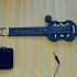 Mini electric guitar for travel. image