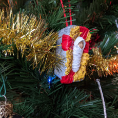 Picture of print of Baby Jesus in a manger Christmas ornament