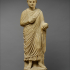 Limestone statue of a wreathed boy holding a ball or piece of fruit image